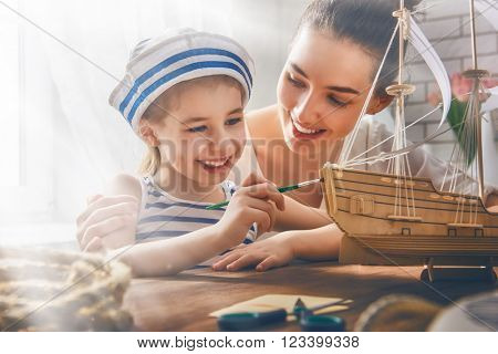 Mother and her child girl making model ship. Dreams of sea, adventures and travel.