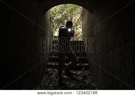Scared Man With A Flashlight Enters Tunnel