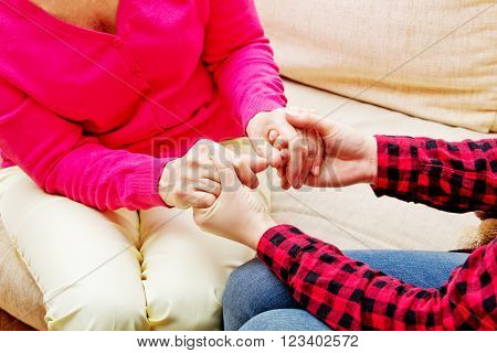 Mother and daughter sitting on couch and holding hands