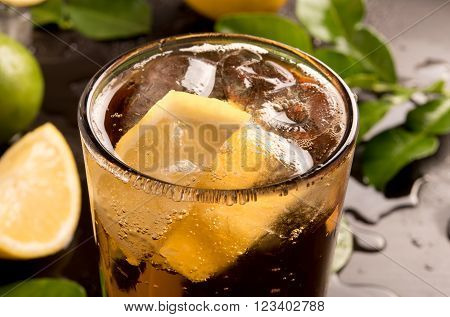 glass of cola or coke with ice cubes lemon slice and mint