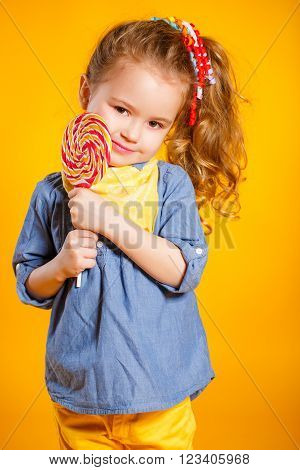 Funny little girl with long, curly red hair,with a yellow handkerchief around his neck, a sweet smile,is dressed in a blue shirt and yellow pants,posing in Studio standing against a bright yellow background, holding a large,round, colourful Lollipop