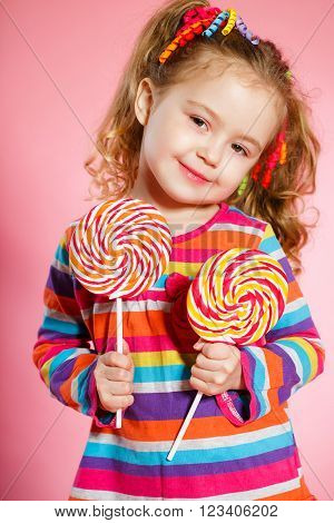 Funny little girl with long, curly red hair,bright ribbons tied into two tails, a sweet smile,wearing a bright dress with a red bow on the chest,posing in Studio on pink background holding two big colorful Lollipop
