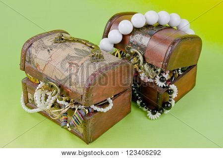 Two Small Boxes With Treasures On A Light Green Background