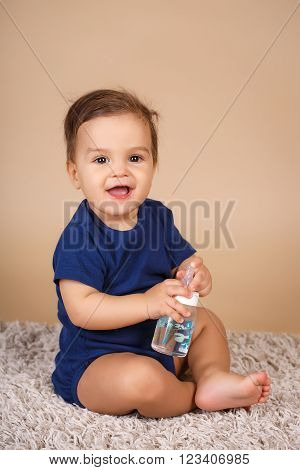 Portrait of a little boy,brunette with brown eyes,dressed in a dark blue suit,barefoot, posing in Studio,sitting on the shag rug on a beige background, with a bottle for baby food,drinking water