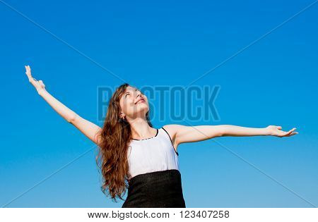 a young charming woman on a background blue sky heaved up hands upwards