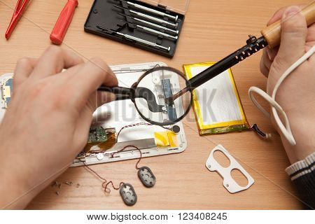 Master Solder Wires Exploded Tablet Computer. He Looks Through A Magnifying Glass.