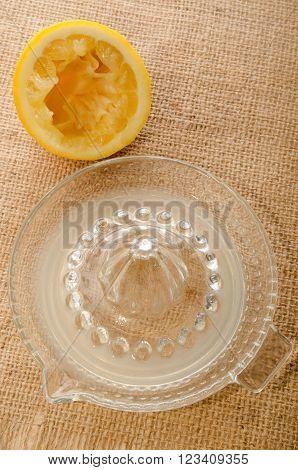 squeezed lemon glass lemon squeezer and fresh lemon juice on jute