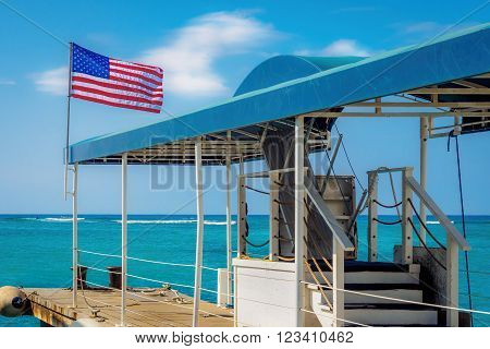 Waikiki, Honolulu, Hawaii, USA - December 13, 2015: Lone jetty or pier flying an American flag. No boats are scheduled to moor at this time.