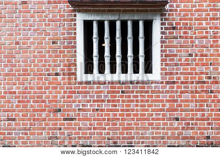 Old red brick wall with White Window.