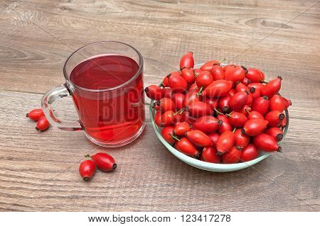 ripe rose hips and a drink in a cup on a wooden background. horizontal photo.
