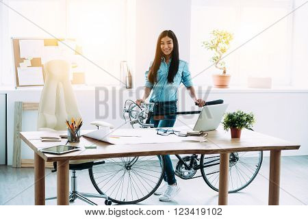 Enjoying her working place. Full length of cheerful young Asian woman leaning to bicycle and looking at camera with smile while standing at her working place