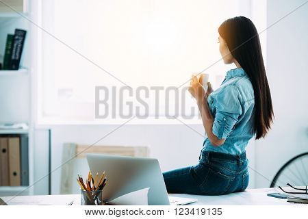 Coffee break. Rear view of young Asian woman holding coffee cup and looking through window while sitting on table at her working place