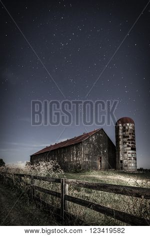 Night time image of an old farm barn and a country road in moonlight
