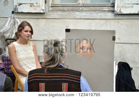 PARIS / FRANCE - September 24 2011: Artist paint a portrait of young woman in Montmartre the famous district of Paris