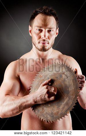 Brutal man holding a circular blade over black