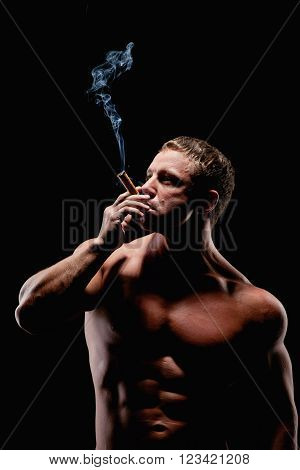 Strong brutal man with a cigar over black