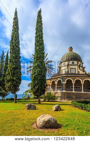 The  Sea of Galilee. The dome of basilica is surrounded by a gallery with columns.  Thick  shadows of palms and cypresses