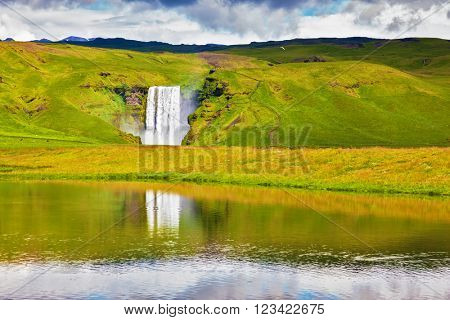 An incredible reflection. Abounding waterfall Skogafoss reflected in  small pond near the road