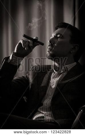 A pensive man smokes a cigar in the room