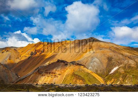 Volcanic summer tundra.  Bright and multi-colored rhyolite mountains - orange, yellow, green and blue. Travel to Iceland in July