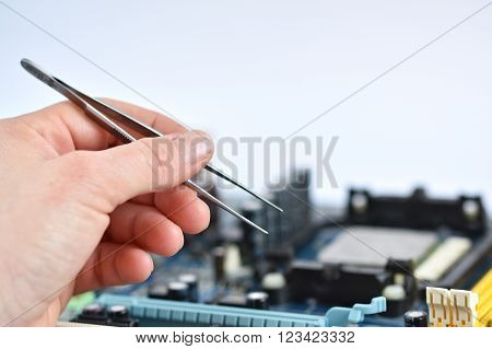 Hand with tweezers above board with components. Repair of computers and modern technologies. PCB.