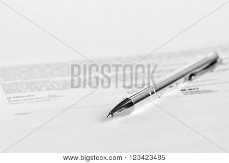 Signature on paper with pen. Isolated on white background.