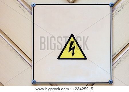 High voltage triangle sign on wooden wall. Electrical hazard sighn on wooden light yellow vintage background.