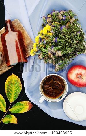 ripe apples in a beautiful plate black background, above view, a bouquet of wildflowers, autumn leaf yellow-green, thick brown bottle, fruit, red apples in a silver plate, lemon yellow, red viburnum