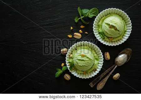 Pistachio ice cream in white bowl, copy space, top view