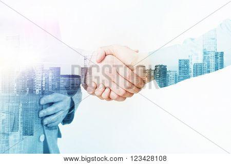 Double Exposure Image of Handshake with Cityline Background