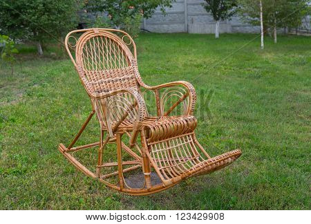 Wicker rocking-chair in the summer garden .