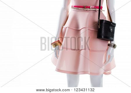 Bracelet and handbag on mannequin. Female mannequin with fashionable accessories. Dark purse and gilded bracelet. Bright dress belts and bracelet.