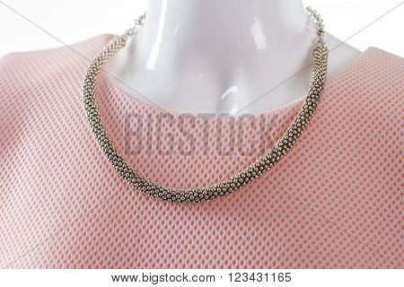 Delicate metal necklace on mannequin. Female mannequin with precious necklace. New arrival at jewelry shop. Charming accessory for women.