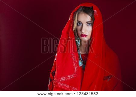 Young beautiful brunette woman in indian red dress