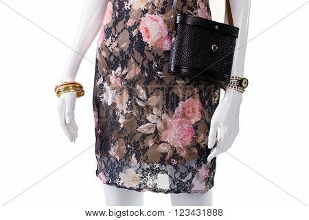 Handbag and watch on mannequin. Female mannequin with luxury accessories. Gold bracelets and leather purse. Woman's wrist accessories on sale.