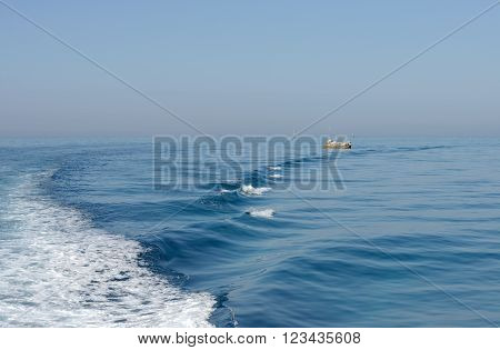 Seascape of with wave on bright blue water and foamy trail astern.