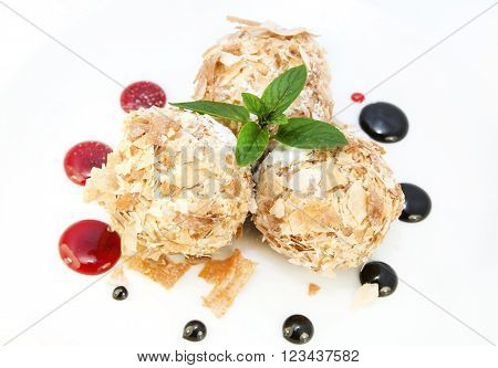 balls of ice cream decorated with mint on a white background in the restaurant