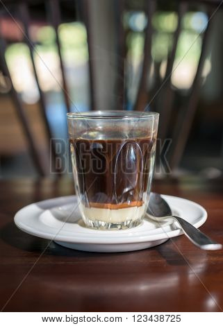 Thai tradition hot coffee with sweetened condensed milk in old style cup served on wooden table.