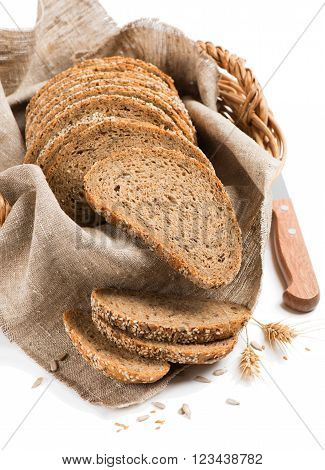 Sliced wholegrain bread in a wicker basket isolated on a white background.