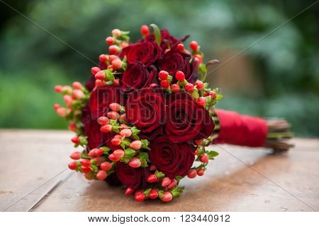 Wedding bouquet of red roses and hypericum, tied with a red ribbon