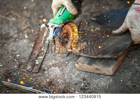 Men sawing metal plate with angle grinder close-up shot ** Note: Shallow depth of field
