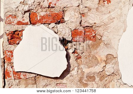 Textured architectural background - aged weathered wall made of red brick with white pieces of old stucco