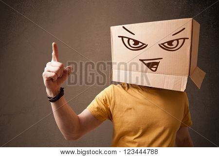Young man standing and gesturing with a cardboard box on his head with evil face