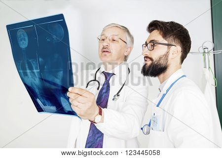 Couple Of Doctors Examining An X-ray Of A Woman's Body