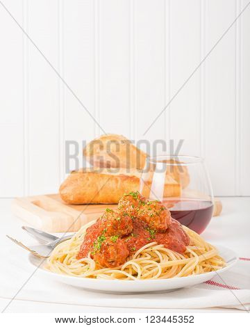 Plate of traditional Italian spaghetti and meatballs with bread and wine. ** Note: Shallow depth of field