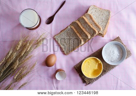 Stiil life with whole wheat bread egg magarine flour and wheat on table