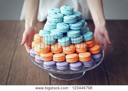 Woman holding varicolored tasty macaroons on glass tray on the table