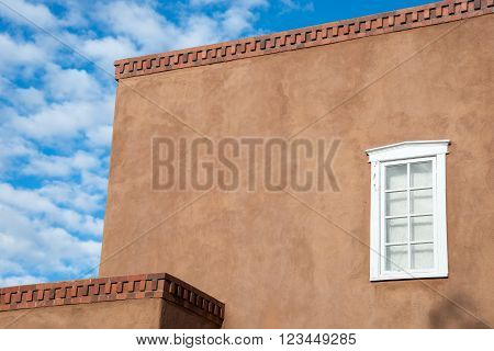Adobe exterior accented with a single white window in Santa Fe New Mexico