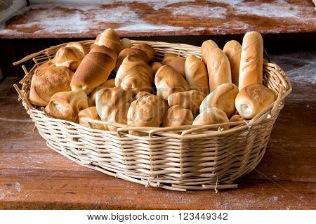 Wicker basket filled with fresh assorted white crusty rolls on display for sale in a bakery on a wooden shelf