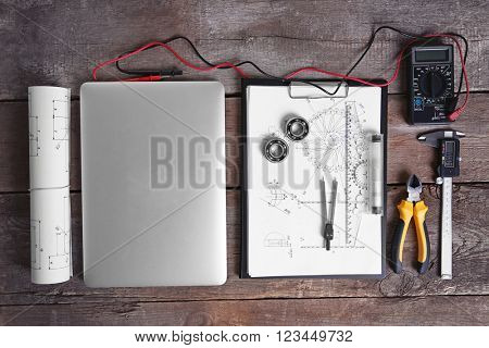 Digital multimeter and laptop on a wooden background.